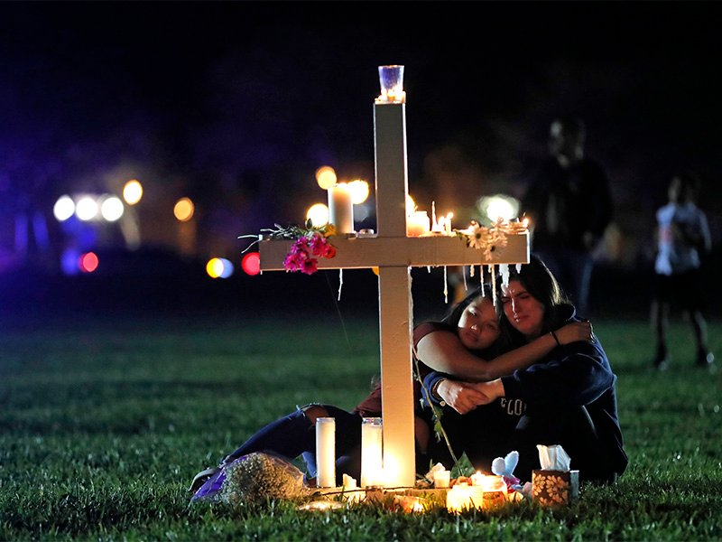 Two people comfort each other as they sit and mourn at one of 17 crosses, each representing a victim, after a candlelight vigil on Feb. 15, 2018 for the victims of the previous day's shooting at Marjory Stoneman Douglas High School in Parkland, Fla.(AP Photo/Gerald Herbert)