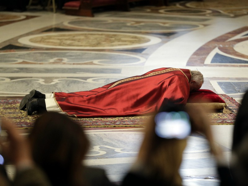 Pope Francis lies down in prayer during the Good Friday Passion of Christ Mass inside St. Peter's Basilica at the Vatican on March 30, 2018. (AP Photo/Andrew Medichini)