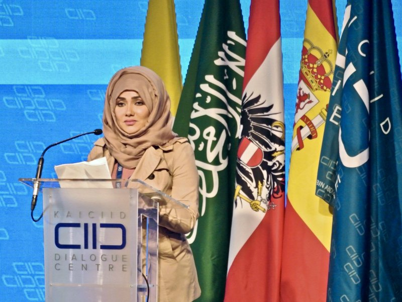 Kowthar Musa Alarbash, a Saudi blogger and member of the kingdom's advisory Shura Council, addresses an interreligious conference in Vienna on February 27, 2018. Behind her are the flags of the Holy See, Saudi Arabia, Austria, Spain and the conference sponsor, the King Abdullah bin Abdulaziz International Centre for Interreligious and Intercultural Dialogue. RNS photo by Tom Heneghan