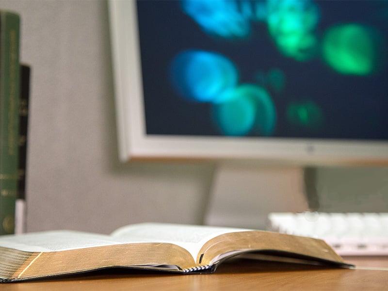 A Bible lies open next to a computer. Photo by Keila Trejo/iadMedia