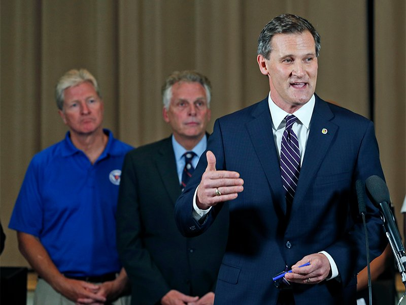 Charlottesville Mayor Mike Signer, right, gestures during a news conference concerning the white nationalist rally and violence as Virginia Gov. Terry McAuliffe, center, and Virginia Secretary of Public Safety Brian Moran, left, listen in Charlottesville, Va., on Aug. 12, 2017. (AP Photo/Steve Helber)