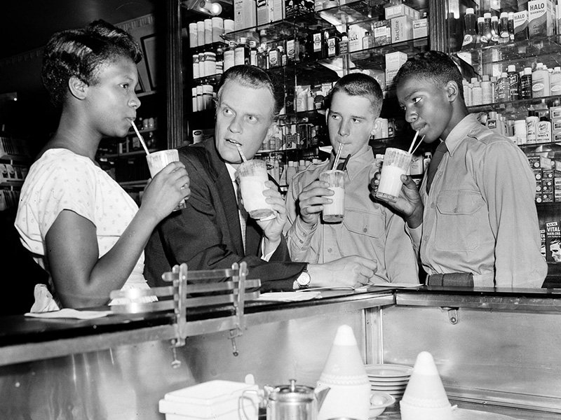 Evangelist Billy Graham drinks an ice cream soda with a group of teenagers after discussing the problem of juvenile crime with a group of youngsters at a New York City news conference on Aug. 8, 1957. At the Hotel New Yorker, Graham proposed that passages from the Bible be read