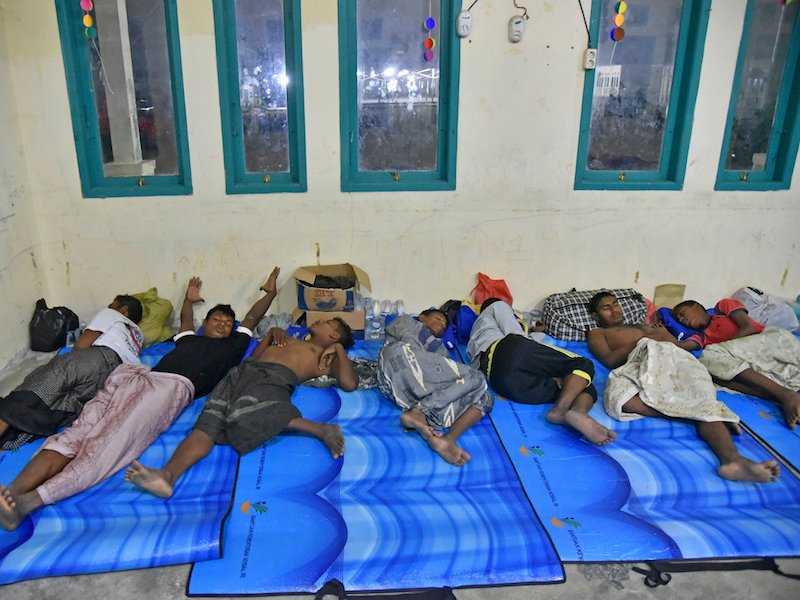 Ethnic-Rohingya men rescued in Indonesian waters sleep at a temporary shelter in Bireuen, Aceh province, Indonesia, Saturday, April 21, 2018. Indonesian fishermen rescued dozens of Rohingya Muslims stranded off the coast of Aceh on Friday, authorities said, in the latest attempt by members of the persecuted ethnic group to flee Myanmar by sea. (AP Photo/Rahmat Mirza)