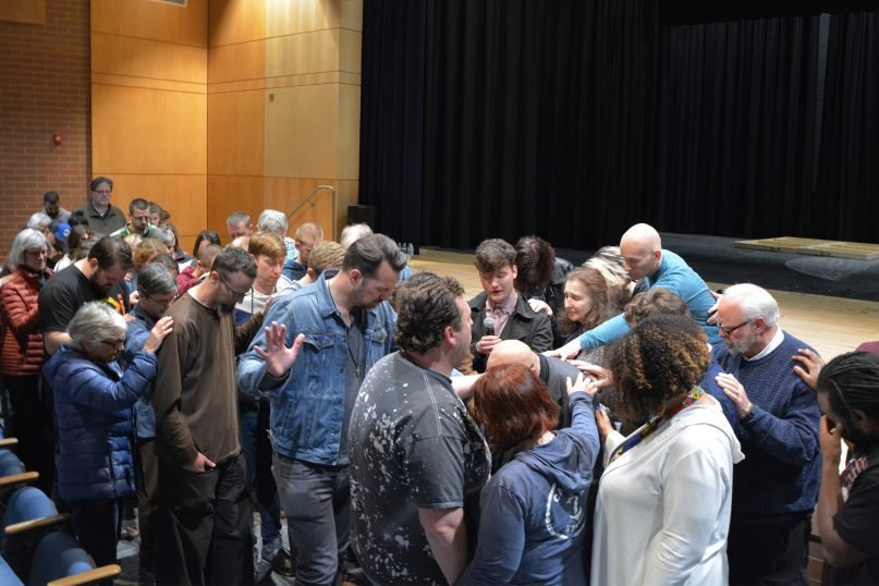 Attendees of the Red Letter Revival gather to prayer over Tony Campolo, bowed at center, in Lynchburg, Va., on April 6, 2018. RNS photo by Jack Jenkins