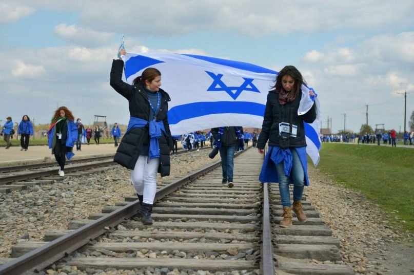 Women carry an Israeli flag while participating in the International March of the Living in 2017.  Participants march between AuschwitztoBirkenau, the largestconcentration camp complex built duringWorld War II. Photo courtesy of Finn Partners