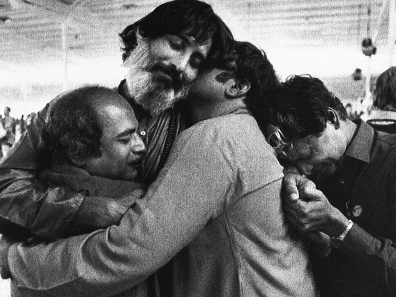 Followers of the Bhagwan Shree Rajneesh embrace during a meditation session on Wednesday, July 4, 1984 at Rajneeshpuram in central Oregon. Followers of the Bhagwan are gathered for their third annual World Celebration. Festivities for the more than 15,000 continue through on Friday. (AP Photo/Bill Miller)