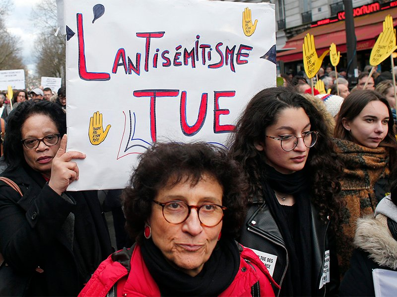 A woman holds a poster reading