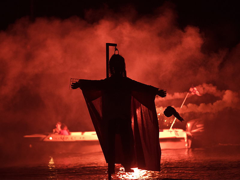 People on a boat hold flares as they sail behind the effigy of Judas during the revival of an old Easter tradition of the