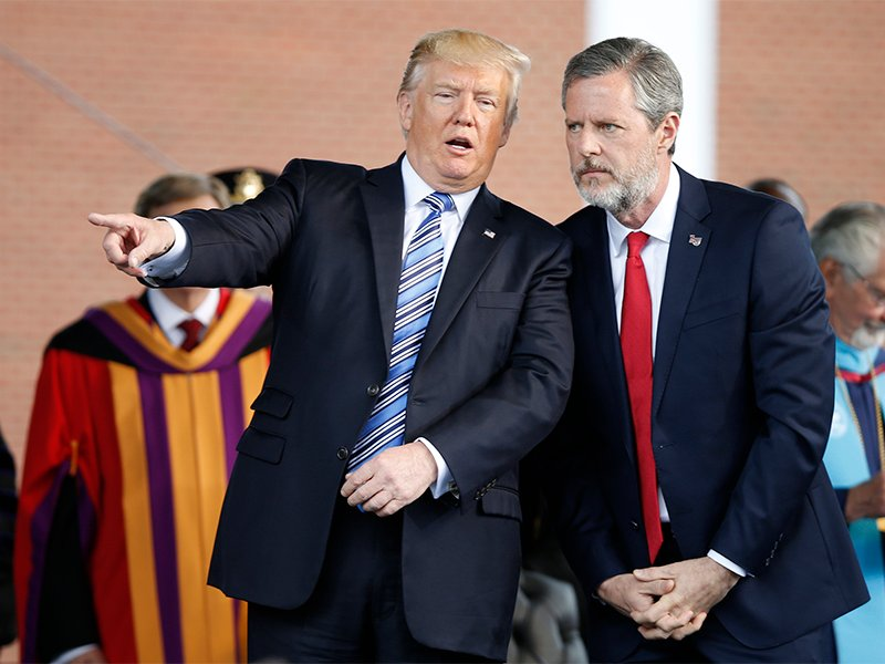 President Donald Trump talks with Liberty University President Jerry Falwell Jr., right, during commencement ceremonies at the school in Lynchburg, Virginia, on May 13, 2017. (AP Photo/Steve Helber)