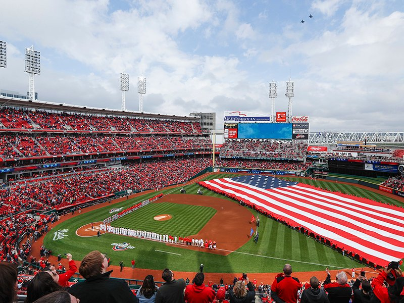 Spectators stand for the national anthem before an opening day baseball game between the Cincinnati Reds and the Washington Nationals on March 30, 2018, in Cincinnati. (AP Photo/John Minchillo)