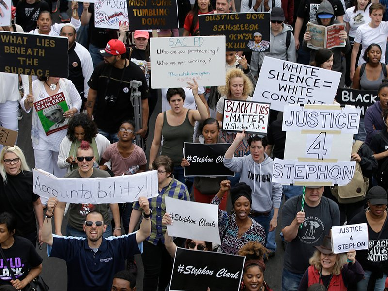 Marchers calling for the indictment of two Sacramento, Calif., police officers who shot and killed Stephon Clark, make their way through downtown Sacramento on April 4, 2018. Clark, who was unarmed, was shot and killed by Sacramento police officers on March 18. (AP Photo/Rich Pedroncelli)