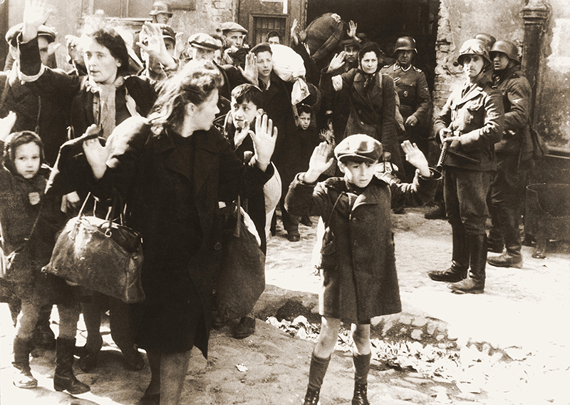 Jewish civilians are forcibly removed from housing blocks by German Nazi soldiers during the Warsaw Ghetto Uprising in April 1943.  Photo courtesy of Creative Commons