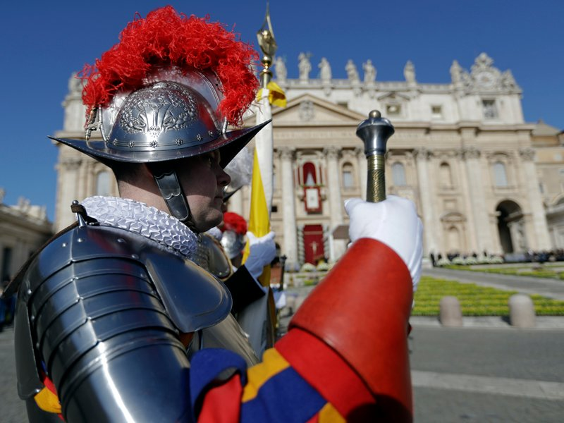 Vatican Swiss Guards stand at attention in front of St. Peter's Basilica at the Vatican prior to the arrival of Pope Francis to celebrate an Easter Mass on April 1, 2018. (AP Photo/Andrew Medichini)