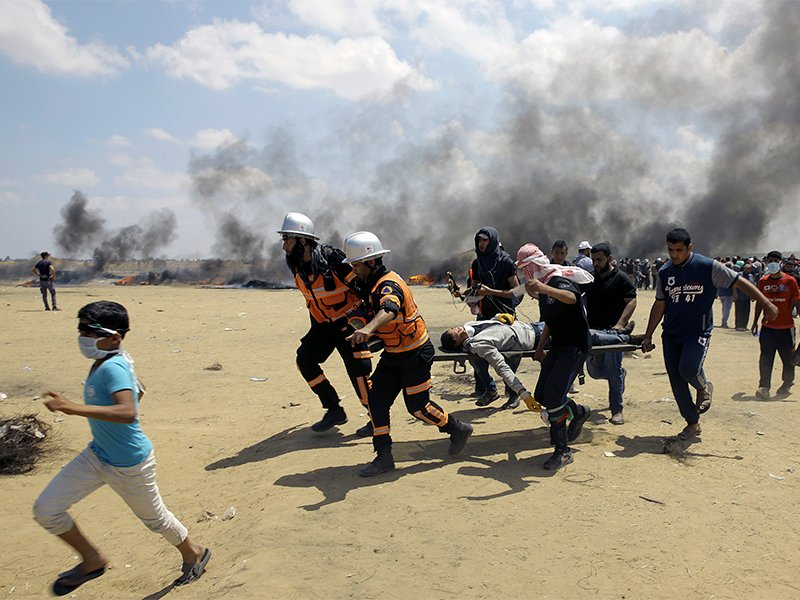 c284432991 Palestinian medics and protesters evacuate a wounded youth during a protest  at the Gaza Strip's border with Israel, east of Khan Younis, Gaza Strip, ...