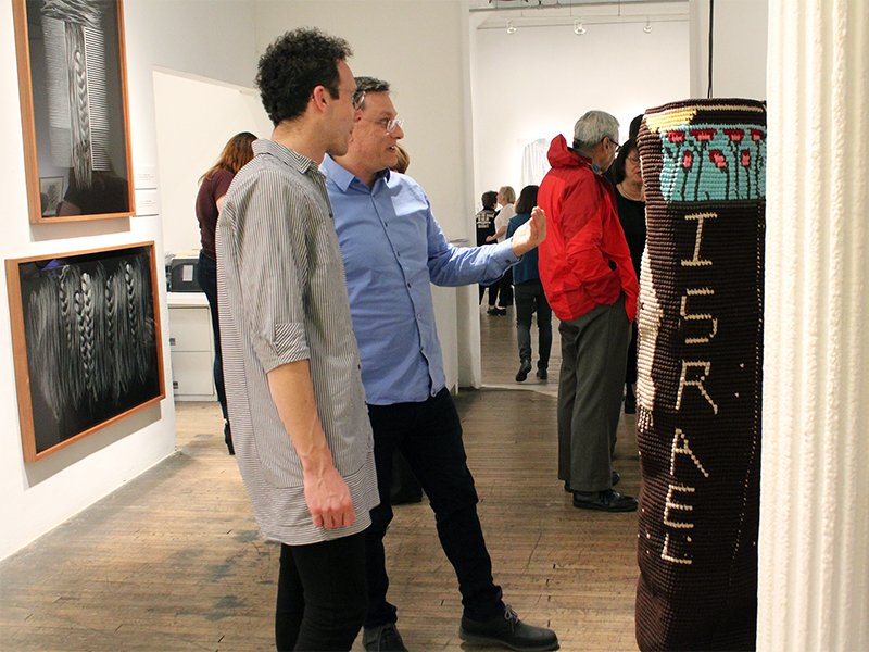 """Artist Gil Yefman, left, and Marco Nocella, from Ronald Feldman Gallery, discuss one of the Kuchinate pieces during the opening of the """"Violated! Women in Holocaust and Genocide"""" exhibit on April 12, 2018, in New York. RNS photo by Liz Donovan"""
