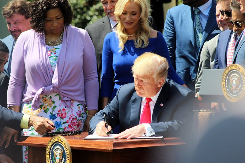 President Trump signs the White House Faith and Opportunity Initiative executive order during a National Day of Prayer event in the Rose Garden of the White House on May 3, 2018, in Washington. RNS photo by Adelle M. Banks