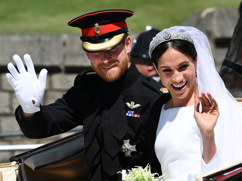 Britain's Prince Harry, Duke of Sussex, and his wife Meghan Markle, Duchess of Sussex, wave from the Ascot Landau Carriage during their carriage procession on Castle Hill outside Windsor Castle in Windsor, England after their wedding ceremony on May 19, 2018. (Paul Ellis/pool photo via AP)