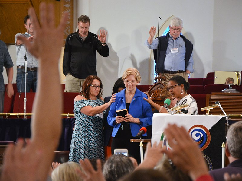 Attendees pray over Sen. Elizabeth Warren, D-Mass., during the Festival of Homiletics at Metropolitan AME Church on May 21, 2018, in Washington. RNS photo by Jack Jenkins