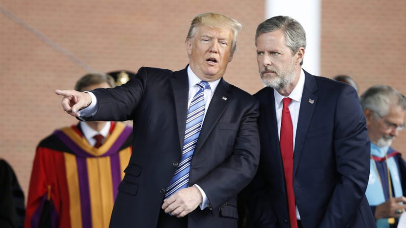President Donald Trump speaks with Liberty University president, Jerry Falwell Jr., right, during commencement ceremonies at the school in Lynchburg, Va., on May 13, 2017. (AP Photo/Steve Helber)