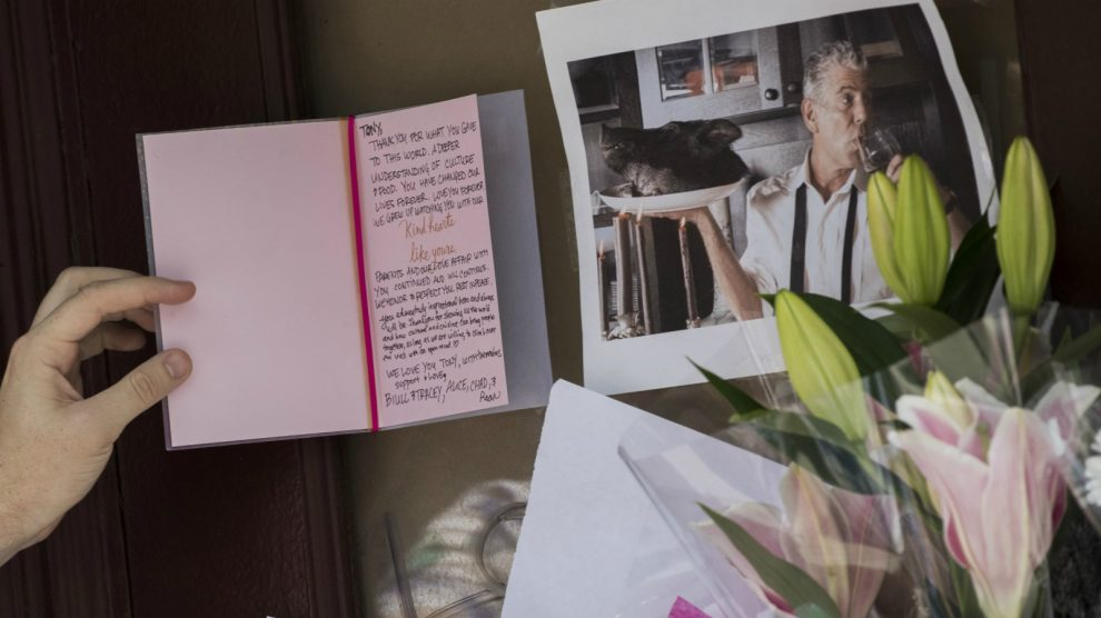 A mourner reads a sympathy card left for Anthony Bourdain