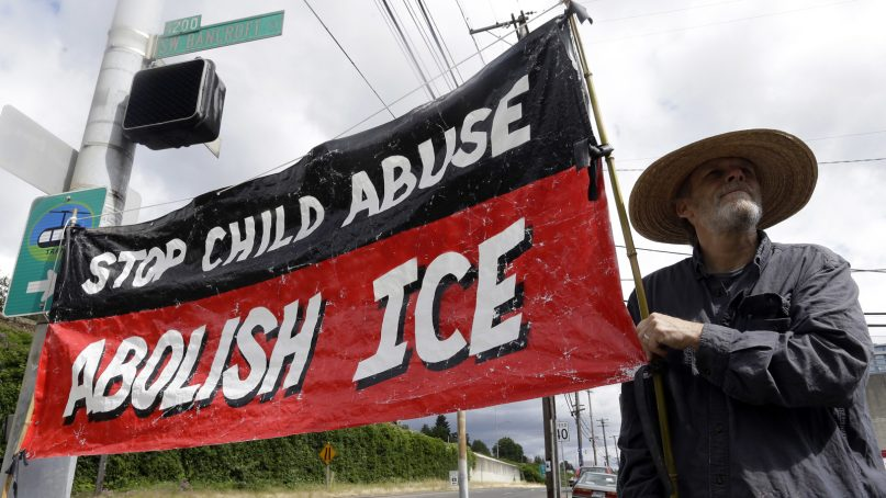 A man, who would not identify himself, holds a sign at a protest camp on property outside the U.S. Immigration and Customs Enforcement office in Portland, Ore., on June 25, 2018. Law enforcement officers began distributing notices to vacate to demonstrators late Monday morning. The round-the-clock demonstration outside the Portland headquarters began June 17, 2018, and increased in size early last week, prompting officials to close the facility. (AP Photo/Don Ryan)