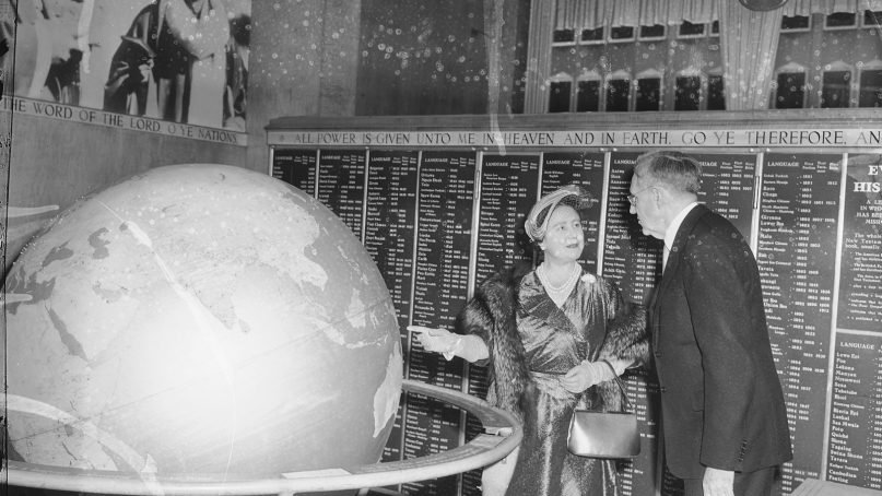 Britain's Queen Mother Elizabeth points to world globe as she chats with Dr. Eric North, secretary of the American Bible Society, during visit to the organization's headquarters in New York City on Oct. 28, 1954. The Queen Mother spent 32 minutes inspecting the society's various departments. (AP Photo/John Lindsay)