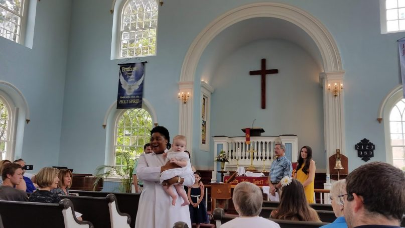 The Rev. Jessica Hayden, pastor of Old Otterbein United Methodist Church in Baltimore, walks down the aisle of her church after baptizing an infant on June 17, 2018. RNS photo by Adelle M. Banks