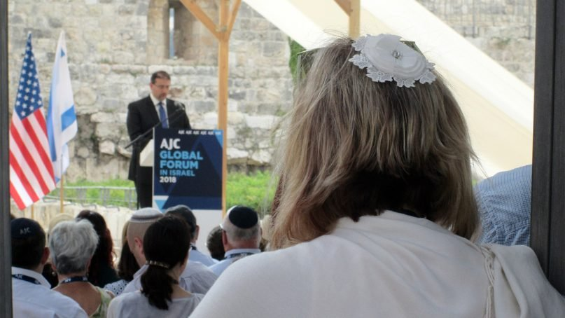 A liberal Jewish woman in a kippah (yarmulke) listens to Dan Shapiro, a former U.S. ambassador to Israel, call for Jewish unity during an American Jewish Committee event in an archaeological garden near the southern end of the Western Wall on June 13, 2018.RNS photo by Michele Chabin