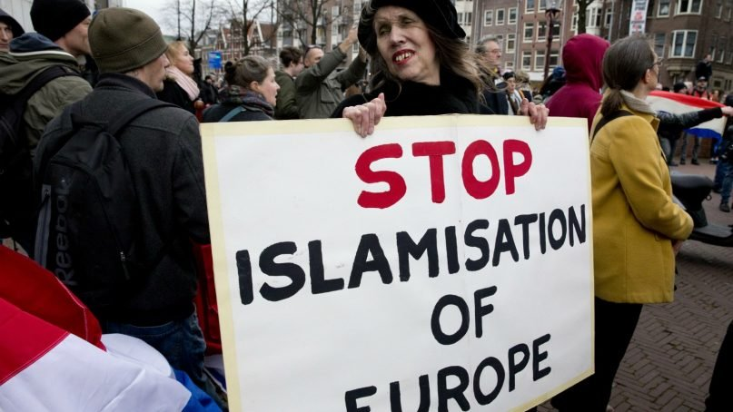 In this Feb. 6, 2016, file photo, a  woman holds a placard during a Pegida demonstration against immigration and Islamization in Amsterdam.  The refugee crisis and the threat of terrorism in Europe are very much related to one another in the minds of many Europeans, according to a survey conducted  by the Pew Research Center across the continent. Many Europeans also worry that migrants will become an economic burden and take away their jobs and social benefits. Populist parties all over the continent have successfully increased their numbers by campaigning against Muslim migrants, including the right-wing Alternative for Germany or Austria's Freedom Party. (AP Photo/Peter Dejong, file)