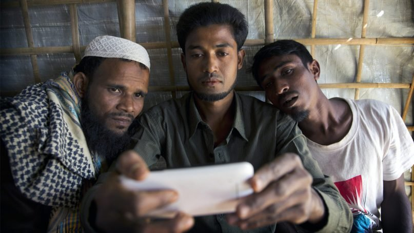 Rohingya Muslim refugee Mohammad Karim, 26, center, shows a disturbing video of mass graves in Myanmar to other refugees in Kutupalong refugee camp, Bangladesh, on Jan. 14, 2018. (AP Photo/Manish Swarup)