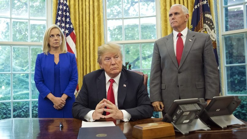 President Trump, center, with Homeland Security Secretary Kirstjen Nielsen, left, and Vice President Mike Pence, right, before signing an executive order to end family separations, during an event in the Oval Office of the White House in Washington, on June 20, 2018. (AP Photo/Pablo Martinez Monsivais)