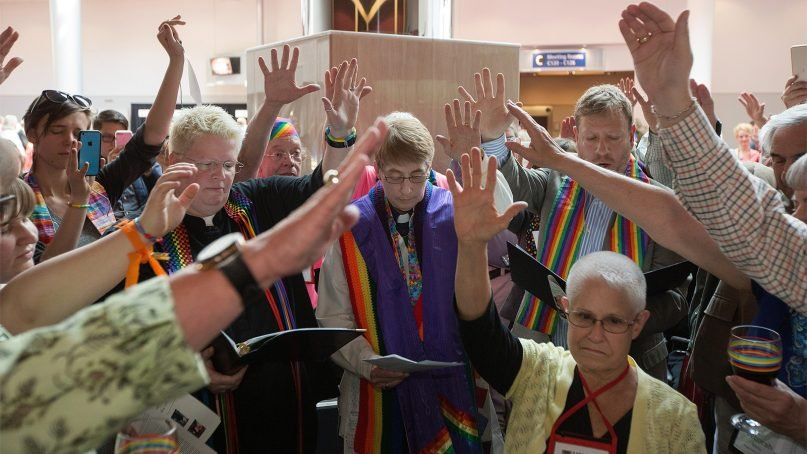 Supporters gather around Susan Laurie, center, during a service of Holy Communion on May 10, 2016, the first day of the 2016 United Methodist General Conference in Portland, Ore. Laurie, a lesbian, was ordained in an unauthorized service in the lobby of the Oregon Convention Center. Photo by Mike DuBose/UMNS
