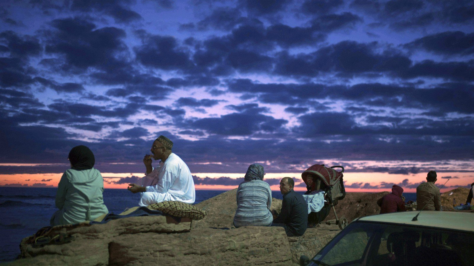 Couples observe the sunset as they break their fast