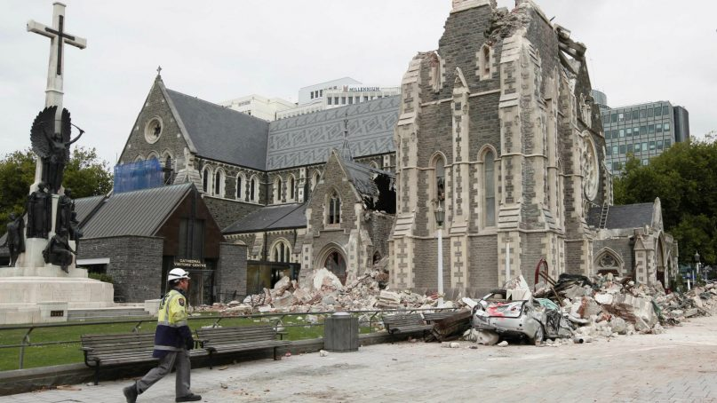 A relief worker walks past the earthquake-damaged Christchurch Cathedral in Christchurch, New Zealand, Saturday, Feb. 26, 2011. Tuesday's magnitude 6.3 temblor collapsed buildings, caused extensive other damage killing more than 100 people and with 200 more missing. (AP Photo/Mark Baker)