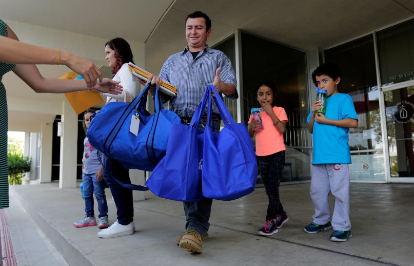 Immigrants from Honduras, Gerarado Reconco Lara, center, with his children Maria, 6, and Gerardo, 8, leave a Catholic Charities facility, Monday, July 23, 2018, in San Antonio. The group was reunited late Sunday night. As the government faces a fast-approaching Thursday deadline to reunite hundreds of families, it is shifting the responsibility for their well-being to faith-based groups primarily in Texas and Arizona. (AP Photo/Eric Gay)