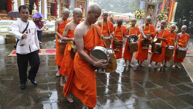 Soccer coach Ekkapol Chanthawong, front, and members of the soccer team who were recently rescued from a flooded cave, attend a Buddhist ceremony as they prepare to be ordained as Buddhist monks and novices in the Mae Sai district, Chiang Rai province, northern Thailand, on July 25, 2018. (AP Photo/Sakchai Lalit)
