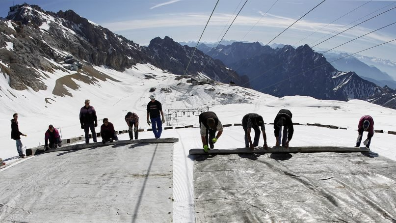Workers cover a glacier with oversized plastic sheets on the peak of Germany's highest mountain, Zugspitze (9,700 feet), in southern Germany, on May 10, 2011. The sheets are meant to keep the glacier from melting during the summer months. It's one proposed geoengineering tactic in the fight against climate change: reflecting sunlight back into space or cooling the planet by sucking heat-trapping carbon dioxide from the air. (AP Photo/Matthias Schrader)