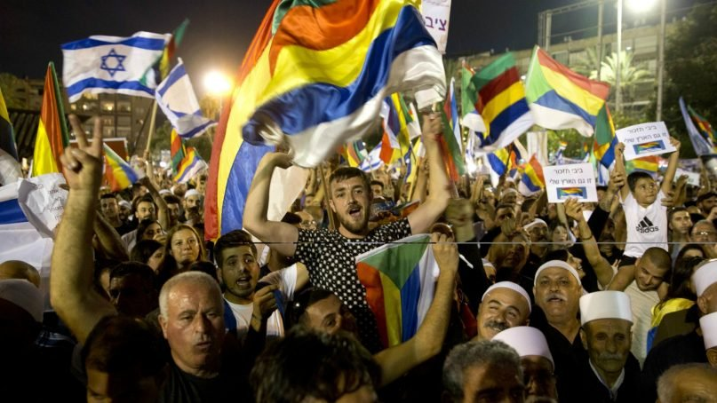 Israelis from the Druze community participate in a rally against Israel's Jewish Nation bill in Tel Aviv, Israel, on Aug. 4, 2018. Thousands of members of Israel's Druze minority and their Jewish supporters packed a central Tel Aviv square Saturday night to rally against a contentious new law that critics say sidelines Israel's non-Jewish citizens. (AP Photo/Sebastian Scheiner)