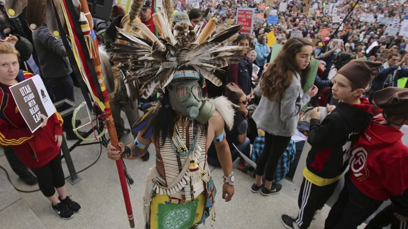 In this Dec. 2, 2017, photo, a supporter of the Bears Ears and Grand Staircase-Escalante National Monuments wears a colorful headdress during a rally against President Trump's reduction of two National Monuments in Salt Lake City. President Donald Trump's rare move to shrink two large national monuments in Utah triggered another round of outrage among Native American leaders who vowed to unite and take the fight to court to preserve protections for lands they consider sacred. (AP Photo/Rick Bowmer)