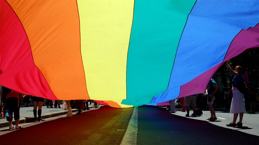 People parade with a pride flag. Photo courtesy of Creative Commons