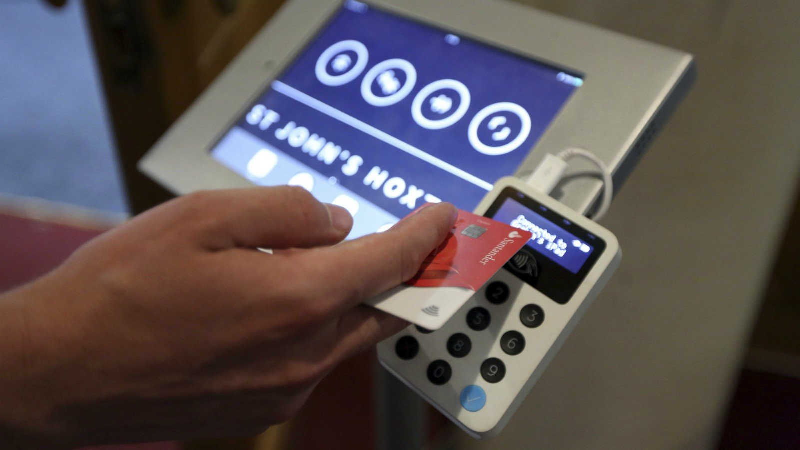 In this photo taken on Aug. 2, 2018, Aaron Rodewald, an operations and finance manager at St. John's Church, demonstrates a device that allows churchgoers to donate money using contactless payments, in Hoxton, London. Thousands of Christian churches across the world are now using portable card readers or apps to take donations as people increasingly stop carrying cash on them. The Church of England says 16,000 religious sites now have access to portable card readers. In the U.S., hundreds of churches have installed kiosks where the faithful can swipe a card to donate. (AP Photo/Robert Stevens)