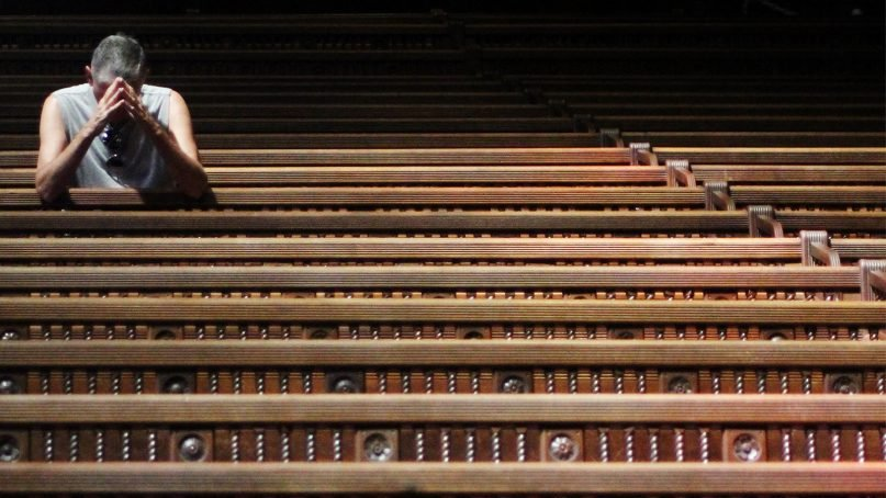 A man kneels in prayer at Trinity Church in Boston in 2013.  Photo by Charles Clegg/Creative Commons