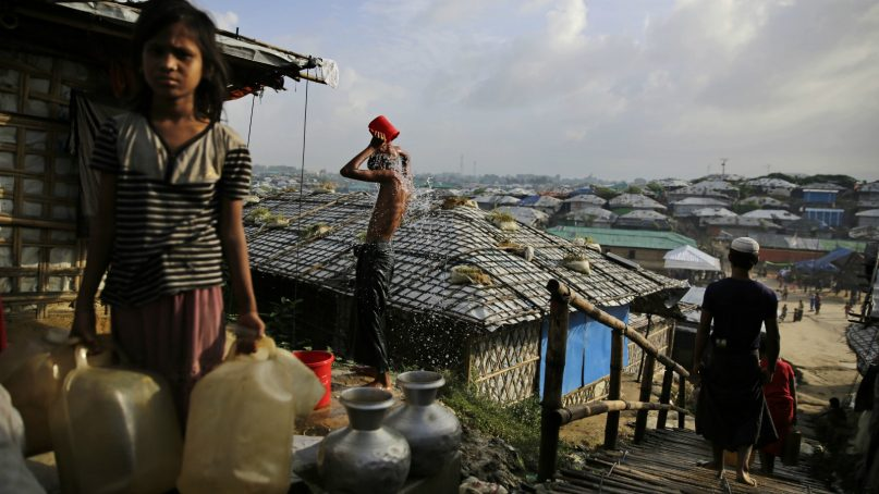 In this Aug. 22, 2018, photo, a Rohingya refugee bathes, as a girl waits to fill water from a hand pump at Kutupalong refugee camp, a ramshackle sprawl of camps built amid low rolling hills and endless monsoon-season mud, in Bangladesh. First built more than 20 years ago by earlier, smaller waves of Rohingya Muslim refugees, the camps in Cox's Bazar district exploded in size when Myanmar's army launched attacks around Aug. 25, 2017, and hundreds of thousands of Rohingya Muslims began flooding across the border. (AP Photo/Altaf Qadri)