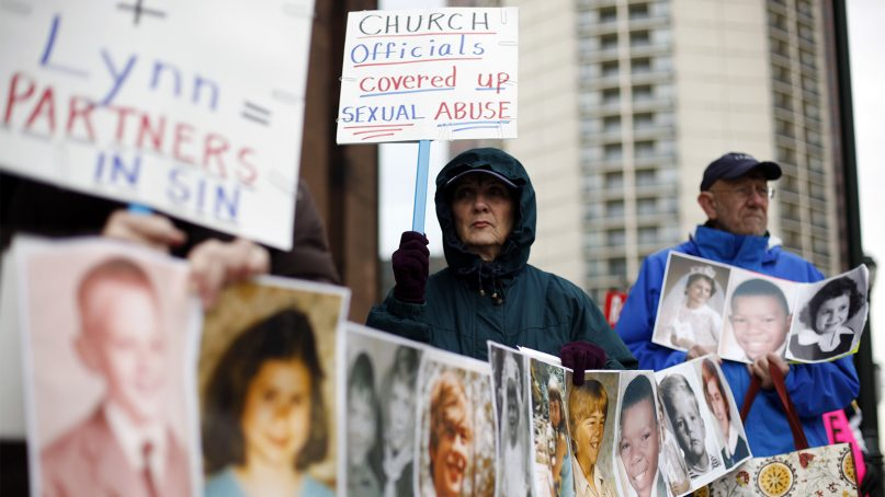 Catherine Coleman Murphy, center, and Jack Wintermyer, right, protest along with others outside Cathedral Basilica of Sts. Peter and Paul before an Ash Wednesday Mass in Philadelphia on March 9, 2011. (AP Photo/Matt Rourke)