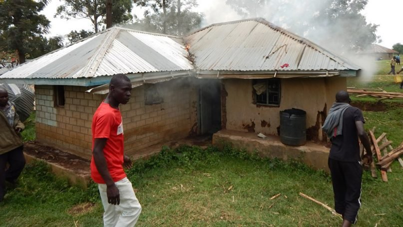 Men burn a house belonging to a suspected witch in northern Tanzania, near the border with Kenya, on Jan 3, 2018. RNS photo by Tonny Onyulo