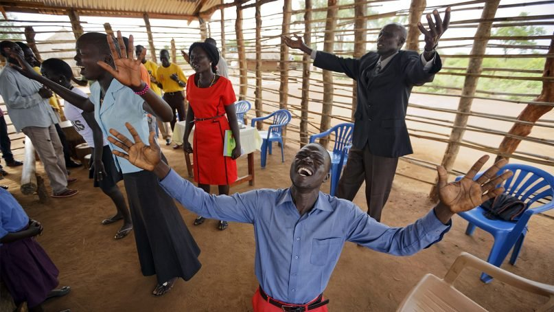 Preacher Daniel Rasash falls to his knees and weeps in prayer at the Yoyo Pentecostal Church in the Bidi Bidi refugee camp in northern Uganda, on June 4, 2017. South Sudanese refugees meet in open-air churches rigged from timber with seats made only from planks of wood or logs drilled into the ground, yet these churches offer support among the daily humiliations that come with rebuilding their lives. (AP Photo/Ben Curtis)
