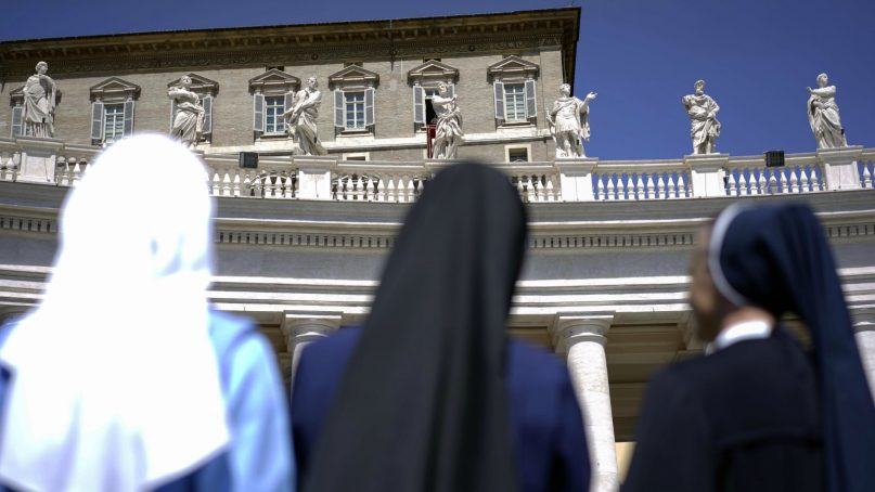 Nuns look up at Pope Francis delivering his blessing during the Regina Coeli prayer he celebrated from the window of his studio overlooking St.Peter's Square, at the Vatican,  on April 21, 2014. (AP Photo/Andrew Medichini)