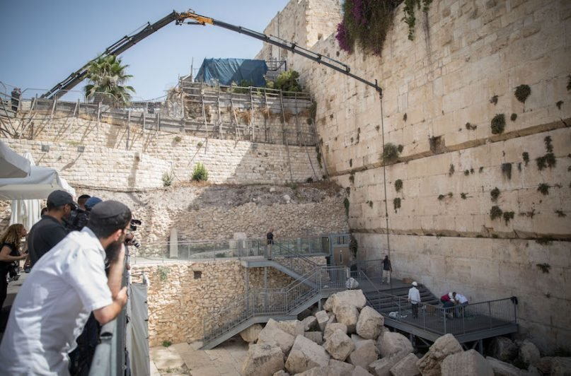 People work to remove by crane a large chunk of stone dislodged from the Western Wall in Jerusalem Old City, at the mixed-gender prayer section on July 25, 2018. Photo by Hadas Parush/Flash90