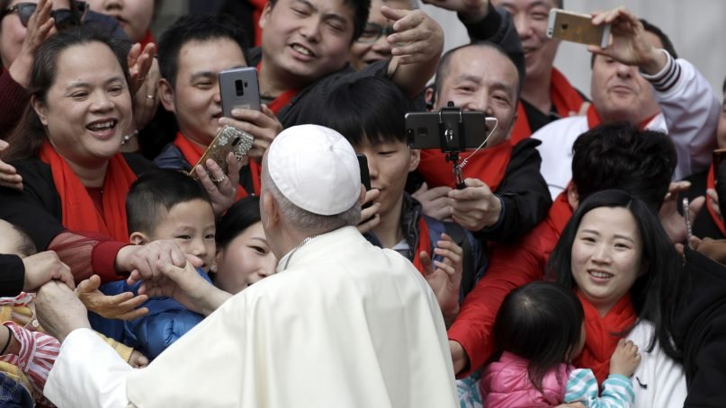 In this April 18, 2018, file photo, Pope Francis meets a group of faithful from China at the end of his weekly general audience in St. Peter's Square, at the Vatican. On Sept. 22, 2018, the Vatican announced it had signed a