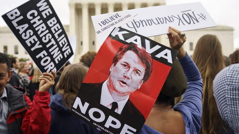 Protesters gather in front of the Supreme Court building holding signs with the image of Judge Brett Kavanaugh that read